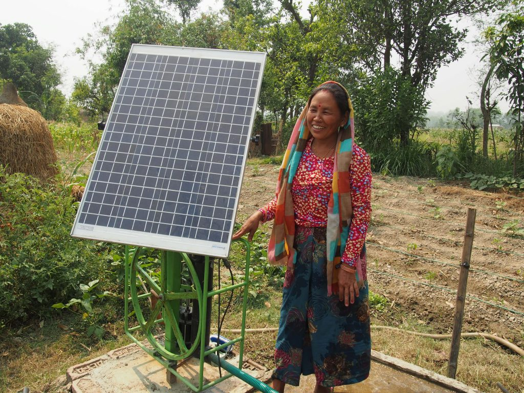 woman standing next to a solar panel in Nepal